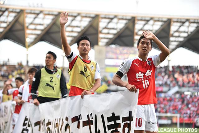「皆さまのご支援ありがとうございます」の横断幕をもってグラウンドを一周する熊本の選手達(2016年5月15日)